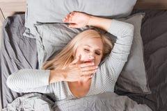 La donna che allunga a letto dopo sveglia immagini stock