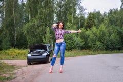 La donna che aspetta per aiutare e che mostra sfoglia su vicino la sua automobile rotta Immagini Stock