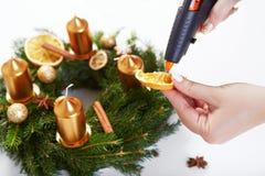 La donna che attacca la pistola di fusione arancio sul Natale si avvolge Fotografie Stock