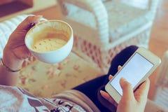 La donna che beve il caffè caldo in caffè ed utilizza un telefono cellulare immagini stock
