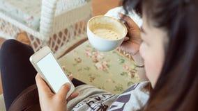 La donna che beve il caffè caldo in caffè ed utilizza un telefono cellulare immagini stock libere da diritti