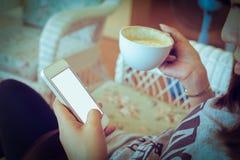 La donna che beve il caffè caldo in caffè ed utilizza un telefono cellulare fotografia stock