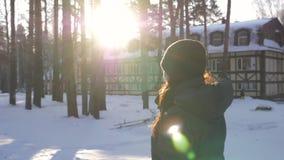 La donna che cammina nel parco nevoso con il sole irradia nell'inverno video d archivio