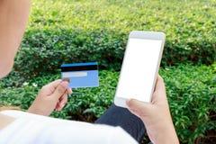 La donna che compera online con lo smartphone dentro si rilassa il parco Fotografie Stock