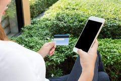La donna che compera online con lo smartphone dentro si rilassa il parco Immagini Stock Libere da Diritti