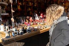 La donna che considera le decorazioni fatte a mano di natale ha fatto da porc fotografia stock