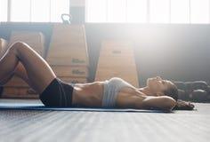 La donna che di forma fisica fare si siede aumenta alla palestra Immagine Stock