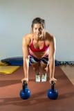 La donna che di forma fisica fare spinge aumenta con i kettlebells Immagine Stock