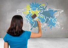 La donna che dipinge una mappa variopinta con pittura ha schizzato il fondo della parete Immagini Stock