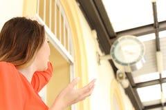 La donna che esaurisce il tempo in una stazione ferroviaria ha ritardato il concetto Immagini Stock