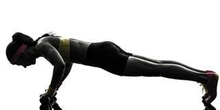 La donna che esercita l'allenamento di forma fisica spinge aumenta la siluetta Immagine Stock