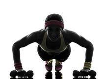 La donna che esercita l'allenamento di forma fisica spinge aumenta la siluetta Fotografia Stock