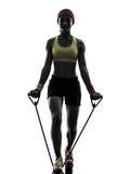 La donna che esercita la resistenza di allenamento di forma fisica lega la siluetta Immagine Stock