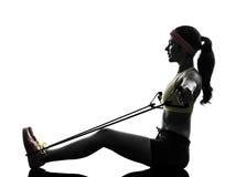 La donna che esercita la resistenza di allenamento di forma fisica lega la siluetta Fotografia Stock