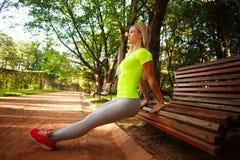 La donna che esile sportiva fare spinge aumenta gli esercizi di forma fisica in parco Fotografia Stock
