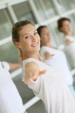 La donna che fa allungando i excercises durante l'yoga classifica nel gruppo Fotografia Stock Libera da Diritti