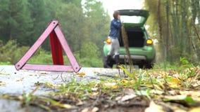 La donna che fa chiamata d'emergenza ai servizi di recupero con l'automobile rotta Triangolo d'avvertimento sulla strada campestr archivi video
