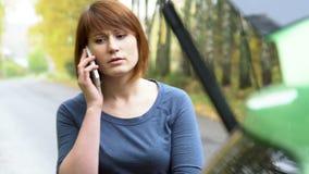 La donna che fa chiamata d'emergenza ai servizi di recupero con l'automobile rotta Triangolo d'avvertimento sulla strada campestr stock footage