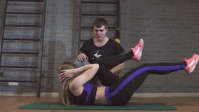 La donna che fa gli scricchiolii addominali preme l'esercizio sulla stuoia con il suo istruttore maschio di sport nello sport di  stock footage