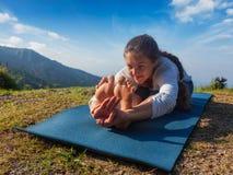 La donna che fa il asana Paschimottanasana di yoga in avanti piega fotografie stock