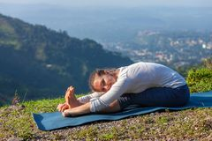 La donna che fa il asana Paschimottanasana di yoga in avanti piega Fotografia Stock