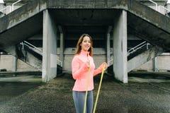 La donna che fa il bicipite martella l'esercizio del ricciolo con la banda della resistenza fotografia stock