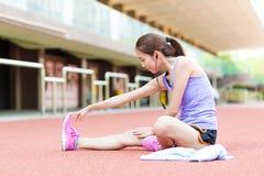 La donna che fa l'allungamento ed ascolta musica nello stadio di sport Fotografia Stock