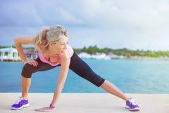 La donna che fa l'allungamento si esercita prima dell'allenamento di mattina all'aperto Fotografia Stock Libera da Diritti