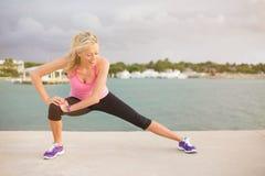 La donna che fa l'allungamento si esercita prima dell'allenamento di mattina all'aperto Immagine Stock