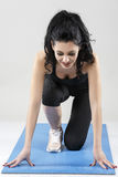 la donna che fa l'allungamento si esercita sull'isolante della stuoia di yoga Fotografia Stock Libera da Diritti