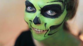 La donna che fa l'arte del fronte del aquagrim su trucco di Halloween con le sue nappe delle mani si inverdisce lo scheletro affa stock footage