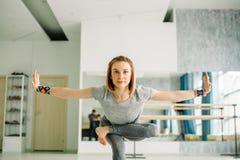 La donna che fa l'equilibratura si esercita durante l'allenamento di yoga in palestra ben illuminata Fotografia Stock