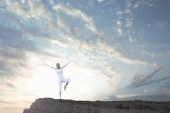 La donna che fa l'yoga si esercita in natura su un'alta scogliera Fotografie Stock Libere da Diritti