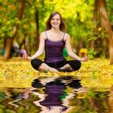 La donna che fa l'yoga si esercita nel parco di autunno Fotografia Stock