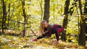 La donna che fa la forma fisica esercita all'aperto Allungamento femminile nella ragazza esile della foresta di autunno all'allen Immagine Stock