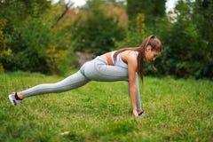 La donna che fa la forma fisica si esercita nel parco dell'estate, allenamento all'aperto Immagine Stock