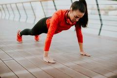 La donna che fa la plancia si esercita sulla passeggiata dopo avere corso in Th Fotografia Stock Libera da Diritti