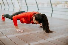 La donna che fa la plancia si esercita sulla passeggiata dopo avere corso in Th Immagini Stock