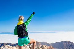 La donna che fa un'escursione il successo arma steso sulla cima della montagna Fotografia Stock