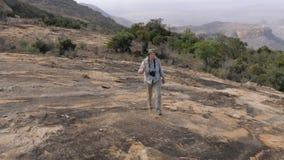 La donna che fa un'escursione su un plateau di pietra su A ha raffreddato Lava To The Top Of un vulcano dormiente stock footage