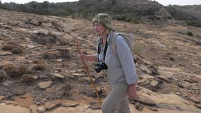 La donna che fa un'escursione su un plateau di pietra su A ha raffreddato Lava To The Top Of un vulcano dormiente video d archivio
