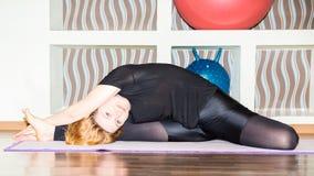 La donna che fanno l'yoga di esercizio e i pilates posano sulla stuoia in palestra Asana Il concetto dello sport, della forma fis Fotografia Stock Libera da Diritti