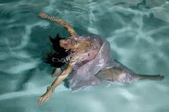 La donna che galleggia sotto l'acqua munisce fuori Fotografia Stock Libera da Diritti