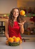 La donna che getta sull'arancia nel natale ha decorato la cucina Fotografia Stock Libera da Diritti
