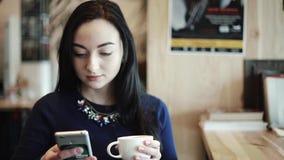 La donna che i quadranti mandano un sms a nelle ricerche di uno smartphone di informazioni su Internet legge gli sguardi alle fot stock footage