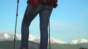 La donna che il viaggiatore costa su un pendio di montagna con i bastoni per seguire Gambe in gran parte archivi video