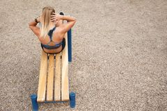 La donna che l'allenamento all'aperto si siede aumenta Fotografia Stock