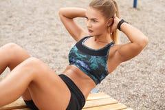 La donna che l'allenamento all'aperto si siede aumenta Fotografia Stock Libera da Diritti