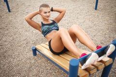 La donna che l'allenamento all'aperto si siede aumenta Immagine Stock Libera da Diritti