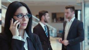 La donna che l'uomo d'affari parla dal telefono stock footage